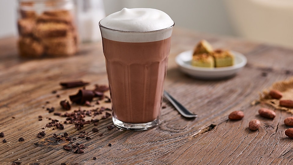 Glass with hot chocolate on wooden table