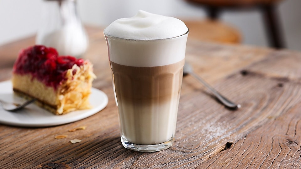 Glass with latte macchiato on table
